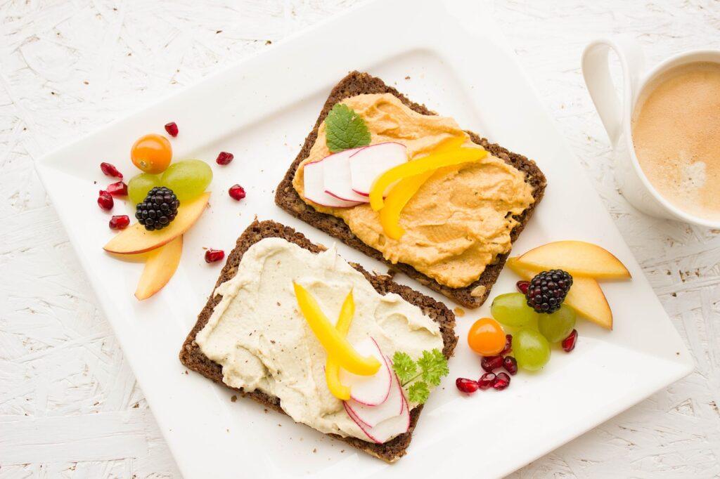 Біла тарілка, на якій знаходяться 2 бутерброди із хумосом і фруктами
