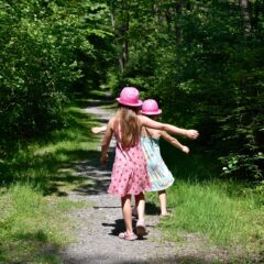 два ребенка бегут по тропинке в лесу